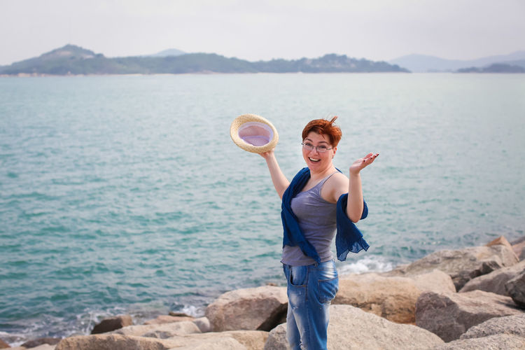 Portrait of cheerful woman standing on rocky shore against cloudy sky