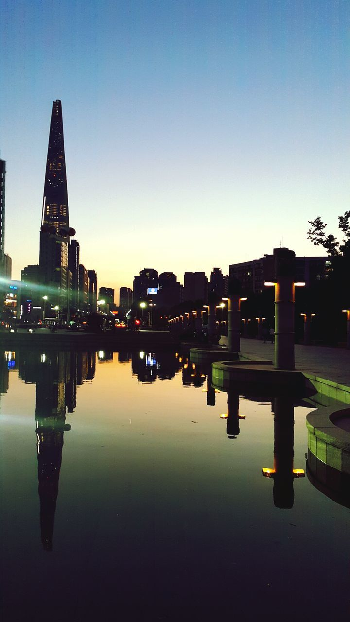 reflection, water, built structure, architecture, waterfront, clear sky, symmetry, building exterior, sky, standing water, outdoors, no people, travel destinations, reflecting pool, lake, illuminated, nature, city, day