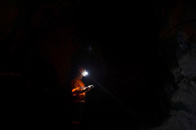 Man with illuminated headlamp in dark cave