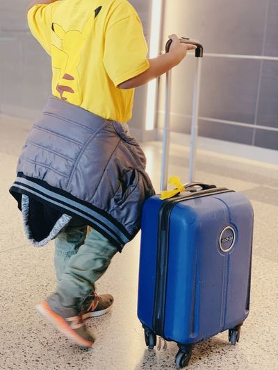 Unaccompanied minor traveling at airport Luggage Suitcase One Person Real People Travel Casual Clothing Holding Low Section Childhood Holiday Flooring Standing Women Shoe Child Jeans Indoors  Clothing Lifestyles Trip