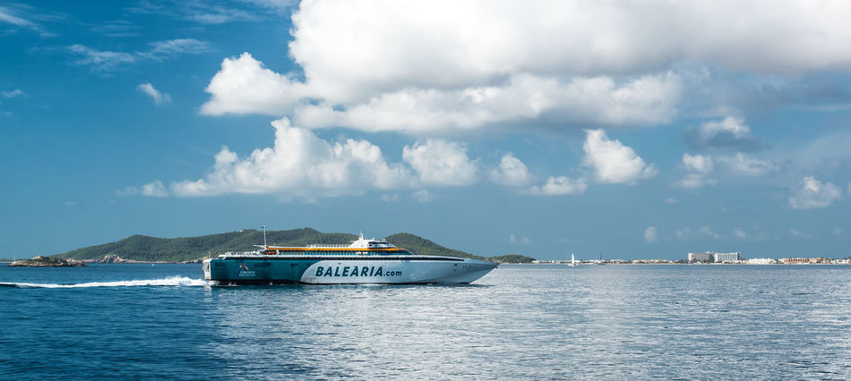 Ibiza, Spain- September 21, 2013: Fast ferry Balearia arriving to the Ibiza port. Balearia is the only ferry operator in Spain that connects the four Balearic Islands to mainland Spain, as well as providing daily sailings between them. Cruise Ship Eivissa Ferry Ferryboat Ibiza Mediterranean  Mediterranean Sea SPAIN Tourist Balearic Islands Cloud - Sky Fast Ferry High Speed Infrastructure Liner Marine Merchant Vessel Nautical Vessel Port Sea Sea And Sky Seaport Seascape Tourism Waterside
