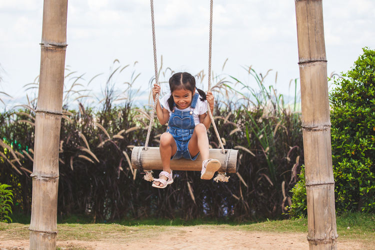 Full length of girl swinging at playground