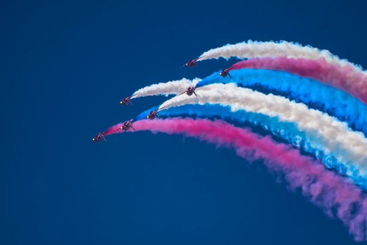 Low angle view of airshow against blue sky