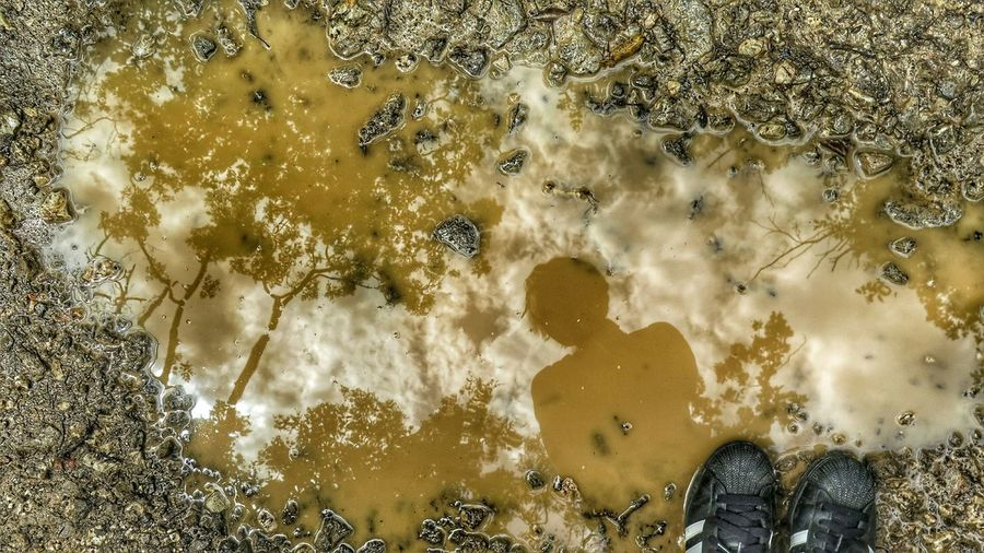 Reflection Of Woman In Puddle