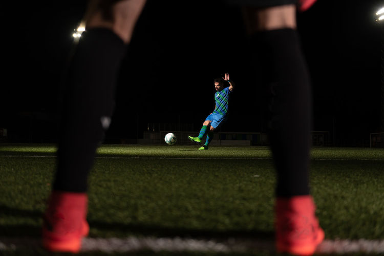 People playing soccer ball at night