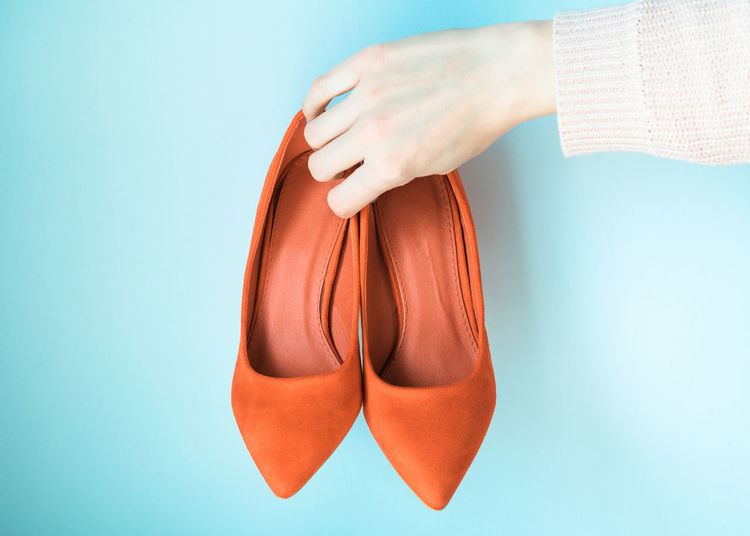 Close-up of woman hand holding shoes against blue background