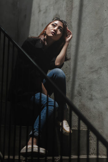 Portrait of young woman standing on staircase against wall