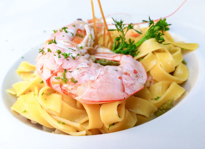 High angle view of tagliatelle and prawns garnished with cilantro served in bowl on table