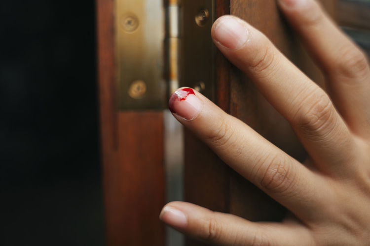 Close-up of injured finger of woman by door