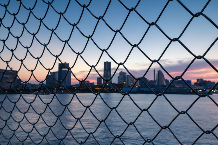 City seen through chainlink fence against sky during sunset