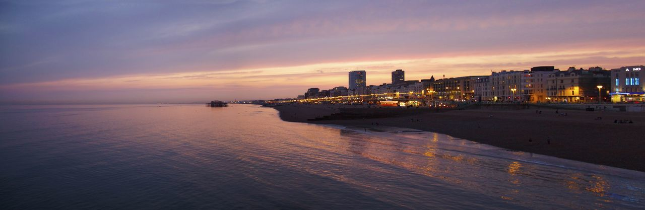 Panoramic View Of Illuminated Buildings By Beach And Sea Against Sky During Sunset