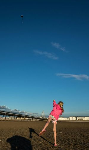 Rear view of girl playing at beach against blue sky