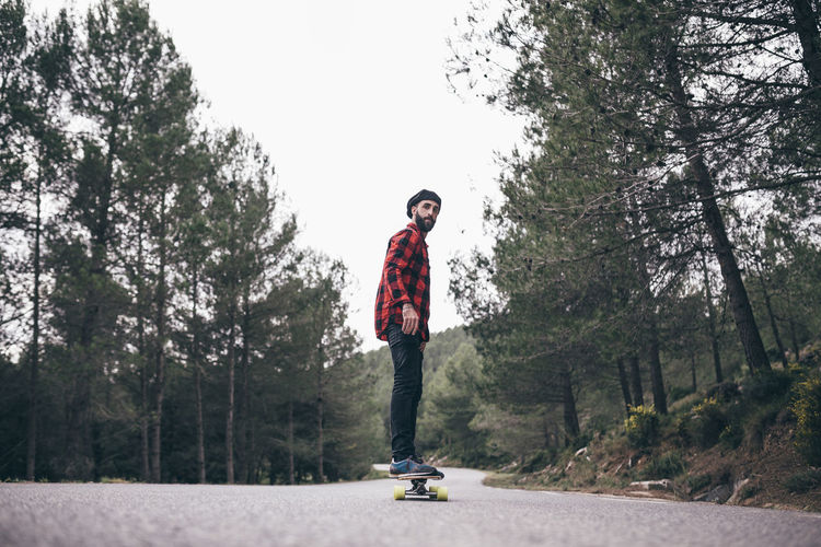 Man Skateboarding On Road Amidst Trees