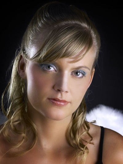 caucasian angel on the black background Beautiful People Slim Standing Angel Angel Wings Attractive Beautiful Woman Beauty Black Background Blond Hair Blonde Hair Caucasian Close-up Contemplation Front View Headshot Indoors  Long Hair Looking At Camera One Person Portrait Pretty Studio Shot Wing Costume Women