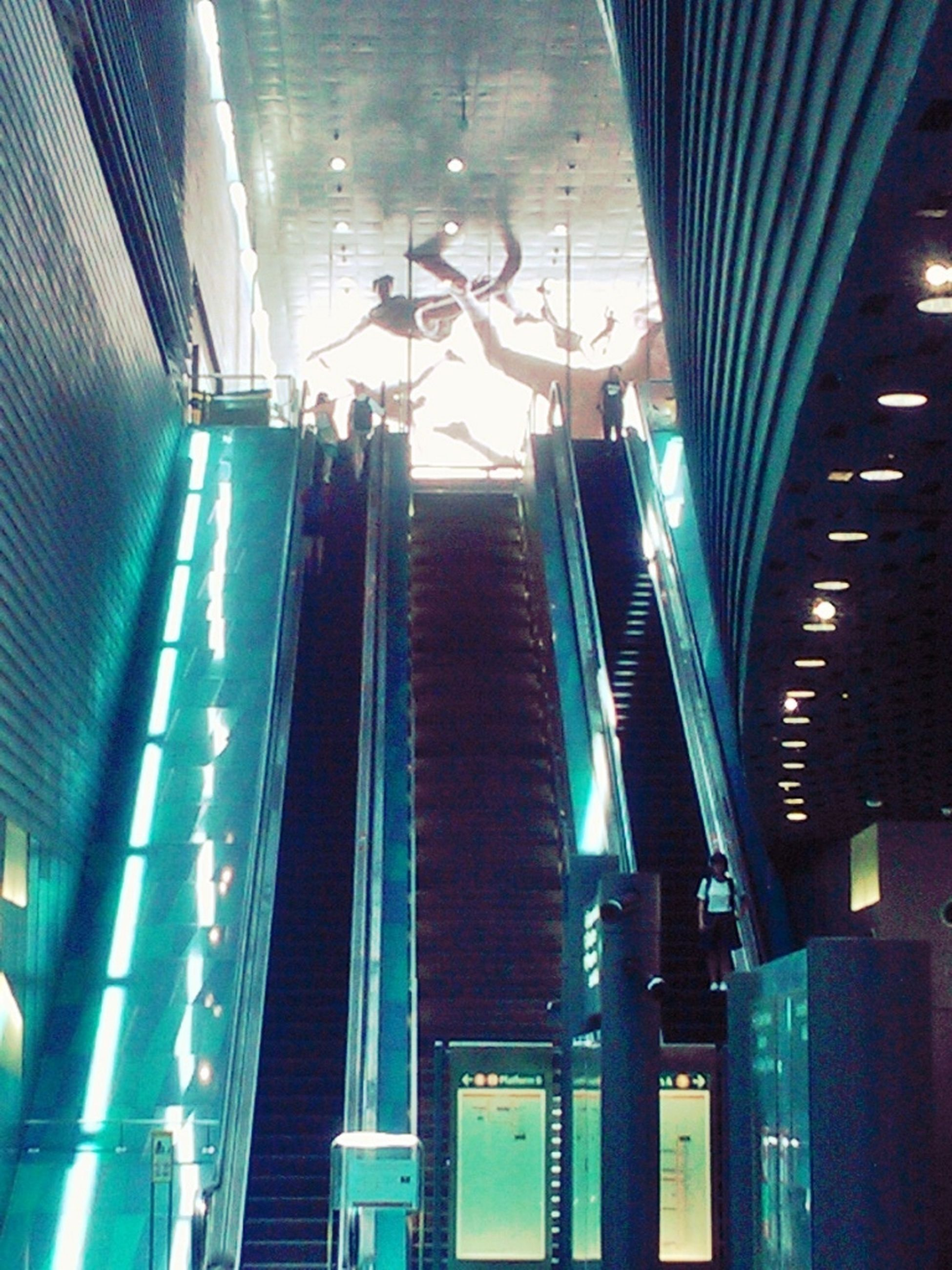 indoors, architecture, built structure, illuminated, modern, low angle view, ceiling, building exterior, escalator, building, reflection, night, lighting equipment, city, no people, blue, railing, diminishing perspective, the way forward, high angle view
