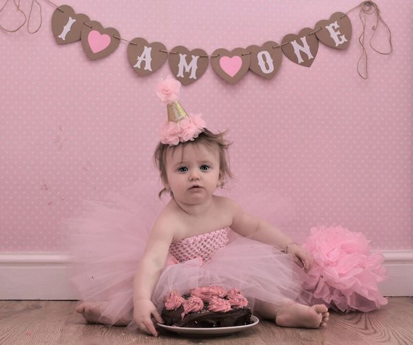 Portrait Of Baby Girl With Birthday Cake Sitting On Floor At Home