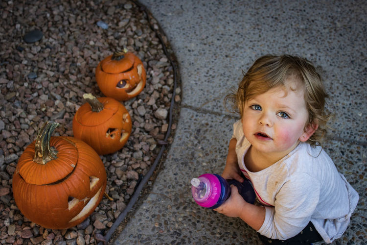 High angle view portrait of girl crouching by pumpkin