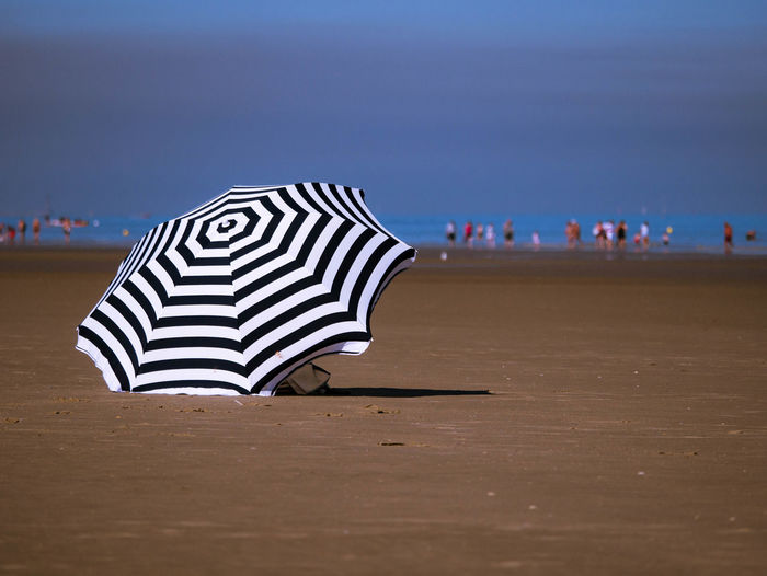 Striped parasol at beach against sky