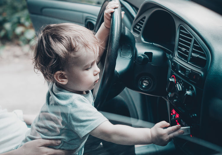 Cute baby boy playing music in car