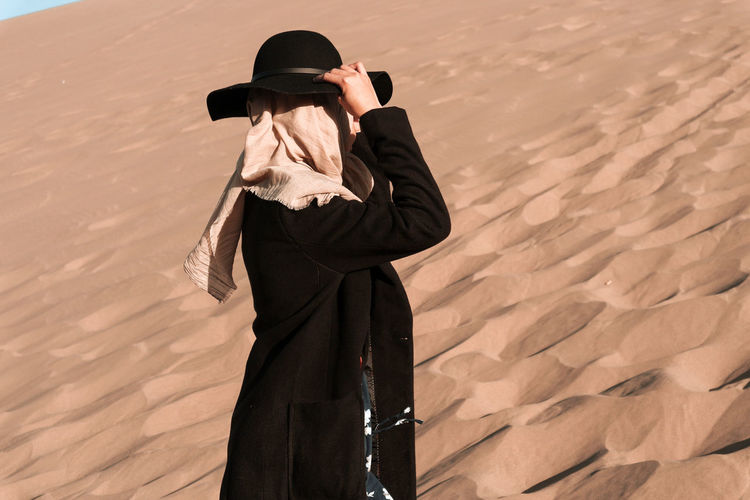 Side view of woman wearing hat and headscarf standing on sand dunes