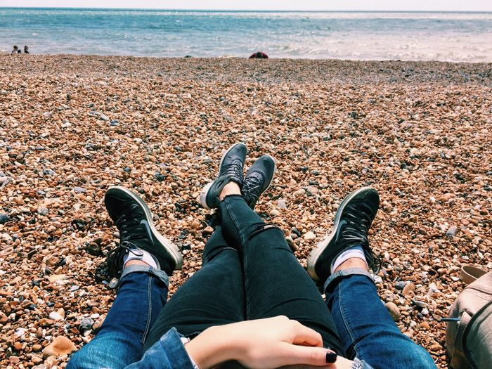 Low Section Of Couple Sitting On Pebble Beach