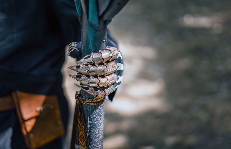 Midsection of warrior holding weapon outdoors