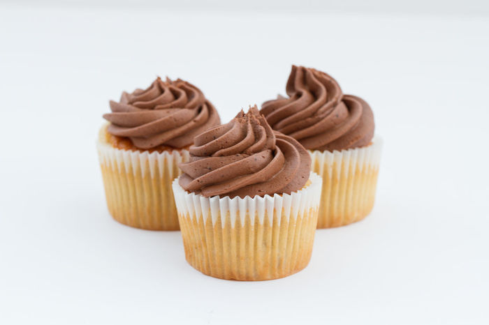 Three chocolate cupcakes with chocolate frosting or icing on an isolated white background. Bake Bakery Baking Bun Buns Cakes Chocolate Chocolate♡ Cupcake Cupcakes Diet Frosting Iced Icing Indulgence Overindulgence Sugar Sugary Sweet Sweet Food Swirl Treat Unhealthy Eating Unhealthyfood White Background