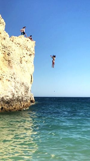 Frau Mut Sprung Klippen Sea Mid-air Jumping Water Clear Sky Rock - Object Full Length Fun Adventure Nature Real People Horizon Over Water Lifestyles Blue Outdoors Vitality