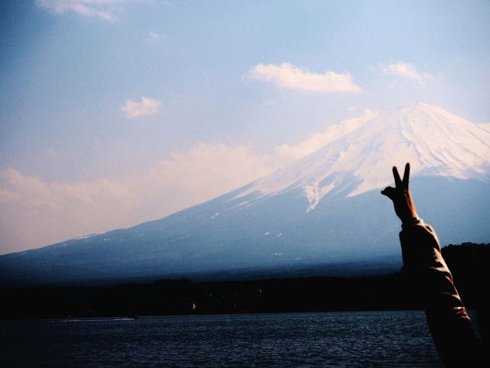 Cropped Hand Showing Peace Sign By Lake Against Mount Fuji