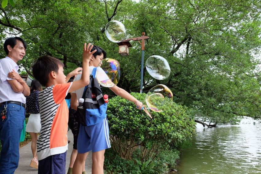 Tree Water Standing Battle Of The Cities Leisure Activity Togetherness FUJIFILM X-T10 Fujifilm_xseries People Green Color Vacations People And Places Streetphotography Bonding Person Holding Plant Young Adult Tourism Vacations Day Green Color Outdoors Nature Looking