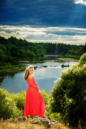 Portrait of woman standing by lake against trees