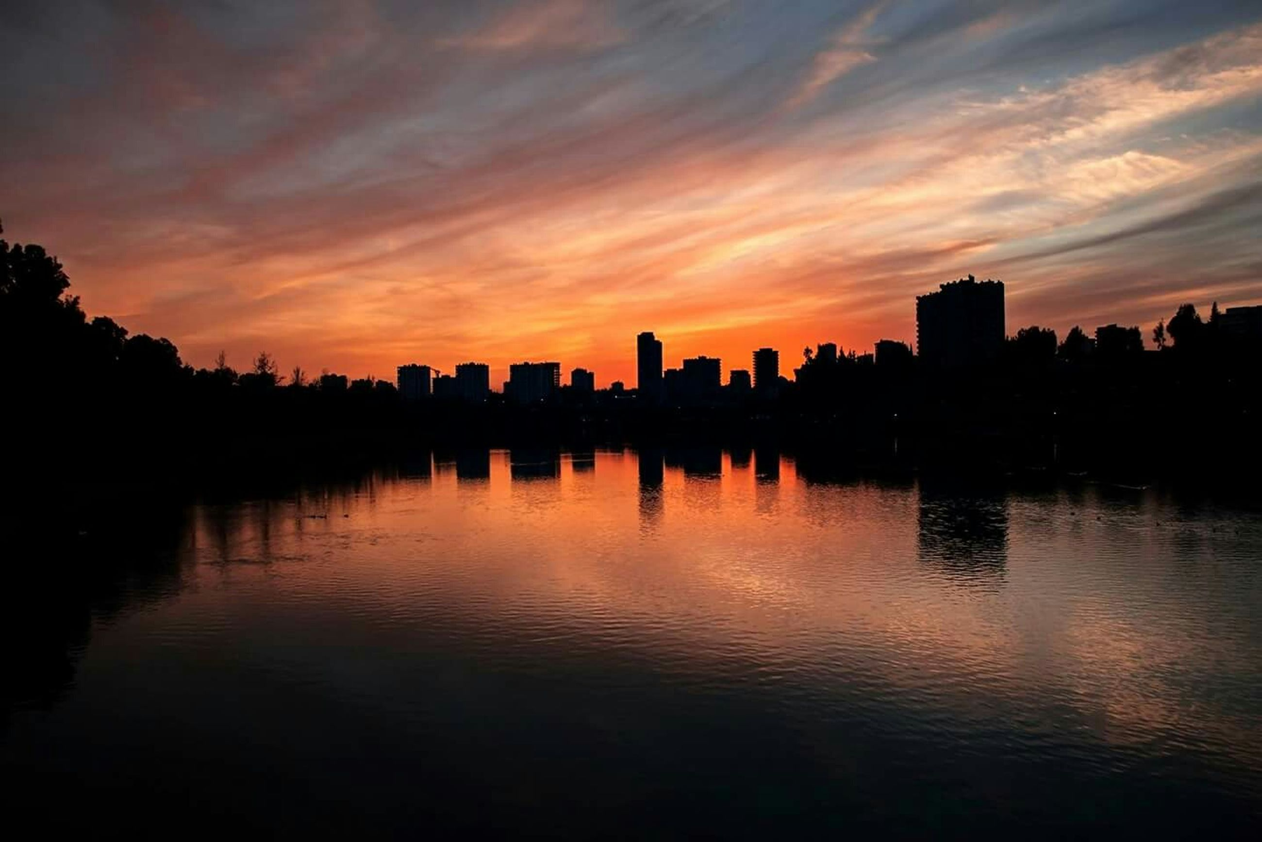 sunset, building exterior, silhouette, architecture, built structure, water, sky, waterfront, city, reflection, river, cloud - sky, orange color, scenics, cloud, lake, beauty in nature, cityscape, dramatic sky, skyline