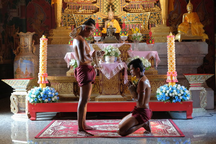 Side view of shirtless men praying in buddhist temple