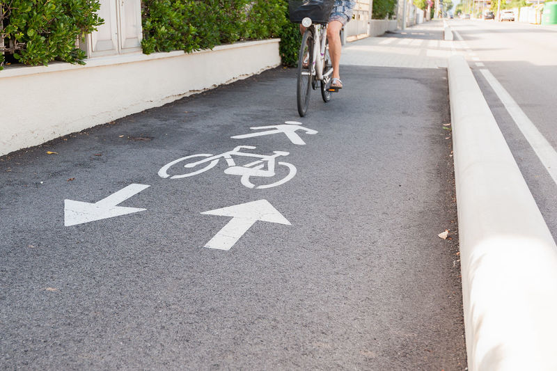 Bicycle road sign and arrow. A bike lane for cyclist. Bicycle Bicycle Lane Communication Cycling Day Low Section One Person Outdoors People Real People Road Road Sign Text Transportation