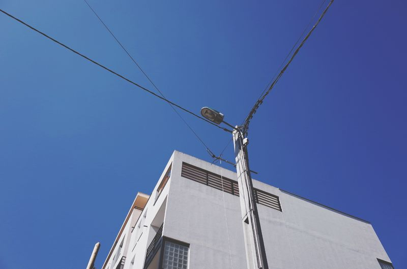 Low angle view of street light and building against clear blue sky