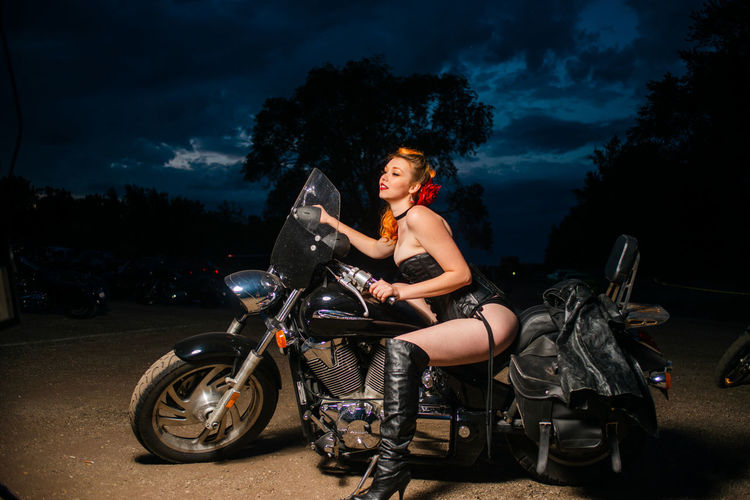 Woman riding motorcycle against sky