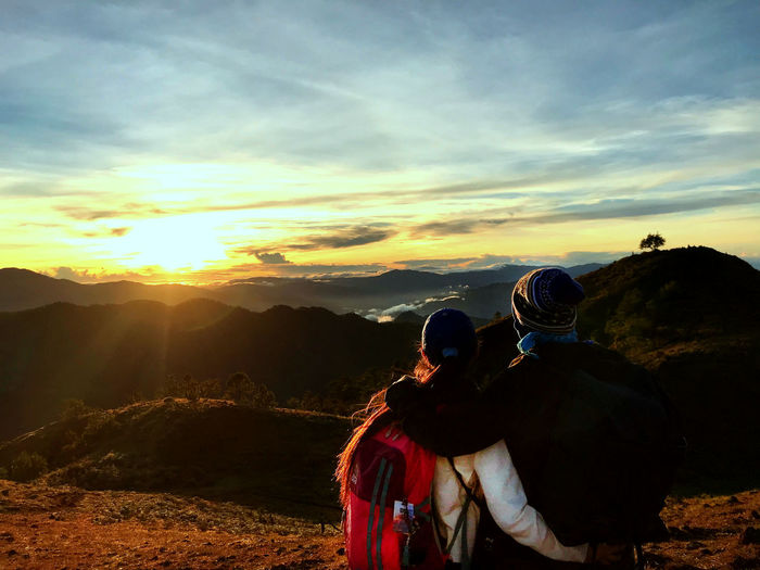 Rear view of couple standing on mountain against sky during sunset