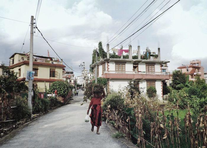 Rear view of people walking on street amidst buildings