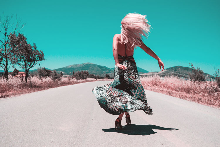 Rear View Of Young Woman Dancing On Road Against Clear Sky