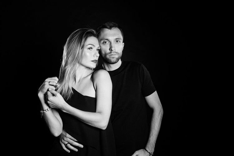 Adult Arm Around Black And White Black Background Bonding Couple - Relationship Emotion Front View Hairstyle Heterosexual Couple Indoors  Love Men Positive Emotion Standing Studio Shot Togetherness Two People Women Young Adult Young Couple Young Men Young Women