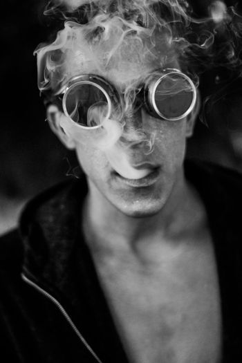 Portrait of young man emitting smoke from mouth