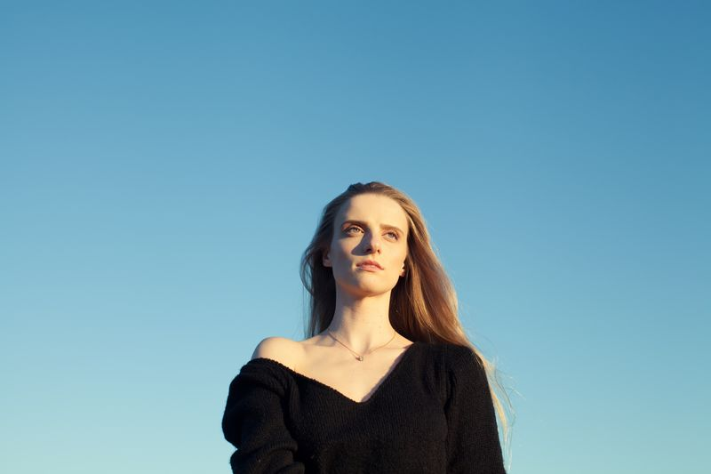 Portrait of a beautiful young woman against clear blue sky