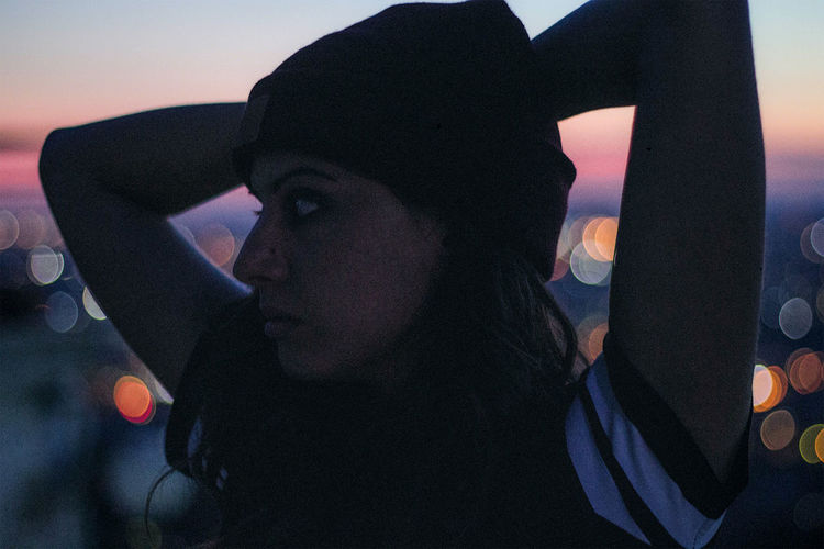 Close-up of young woman hands against sky during sunset