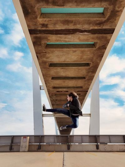 Woman Jumping Over Bridge Against Sky