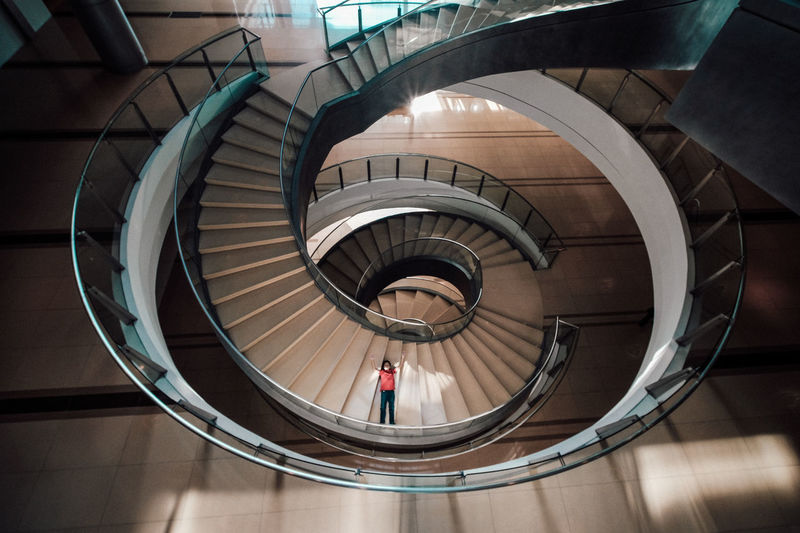 Boy Lying On Steps Of Spiral Staircase