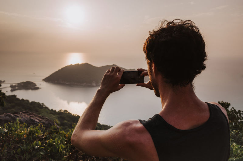Rear view of man photographing sea against sky during sunset