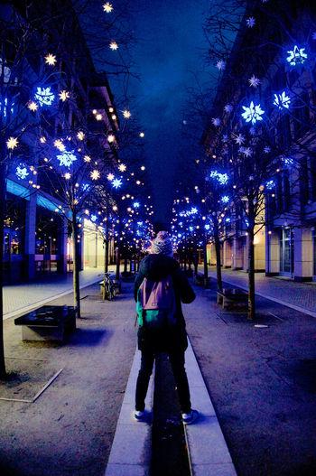 People walking on illuminated city at night