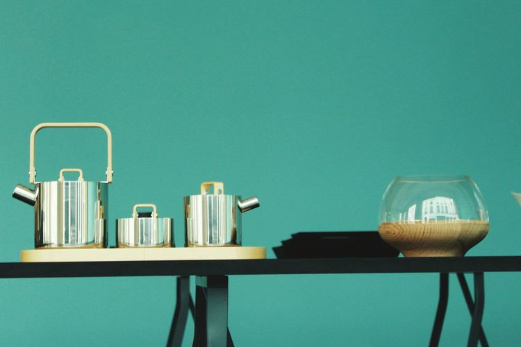 Close-up of teapots on table against blue background