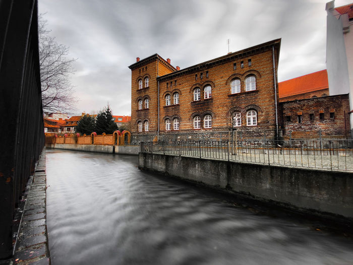 Canal by buildings in city against sky