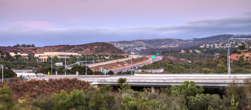 Highway in Irvine, California, at sunset with mountain range in the distance in summer 73 California Light Trails Panorama Panoramic Pink Sky Road Sky And Clouds Skyline Southern California Travel Trip USA United States View Adventure America Highway Irvine Journey Mountains Orange County Sky Sunset Toll Road